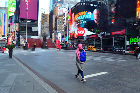 A lone woman takes a walk through an unusually empty Times Square following the shelter in place order