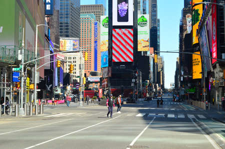 A few straggling pedestrians walk through a deserted Times Square following a shelter in place order due to coronavirus Editorial