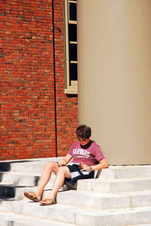 A young student studies on the steps of Harvard Memorial Church