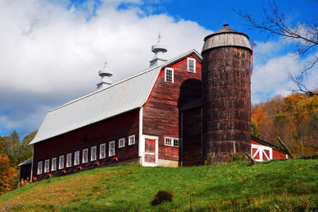 A long barn stands on top of a hill in Autumn on a Vermont farm
