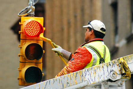 City Worker Gives a New York City Street Light a Fresh Coat of Yellow Paint