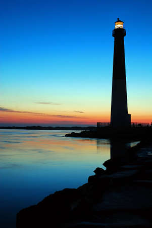 Barnegat Light shines against a sunrise sky on the New Jersey Shore