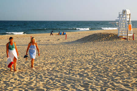 Two Adult women exit the beach on a late summer's afternoon in East Hampton, New York