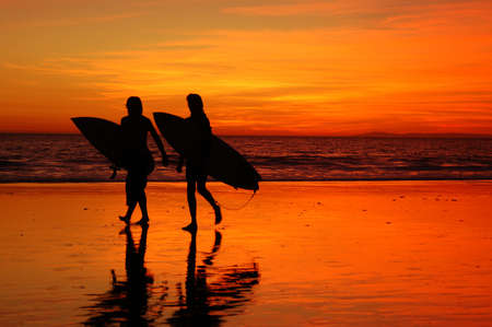 Two teenager surfers leave the ocean at the day's end
