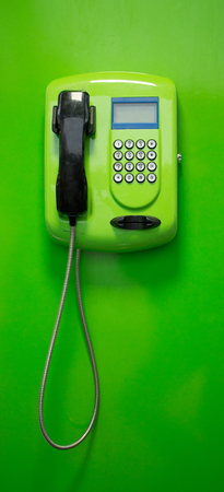 payphone: Green payphone with a black tube on a green background,