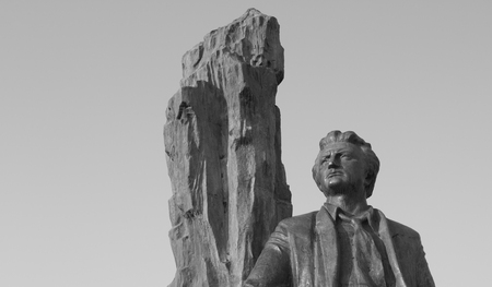 parget: A stone statue of a man against a white sky. The black and white picture