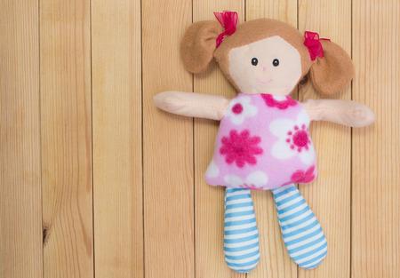 niños vistiendose: Mullido, juguete de una hermosa muchacha en una tabla de madera