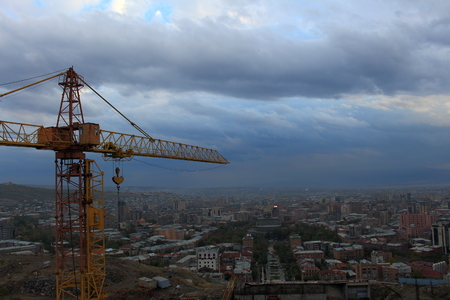 orange high construction crane against the background cityscape, of the blue sky and clouds Stock Photo
