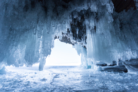 Baikal Lake in the winter. View from the ice grotto in the coastal rocks to the strait Maloye More