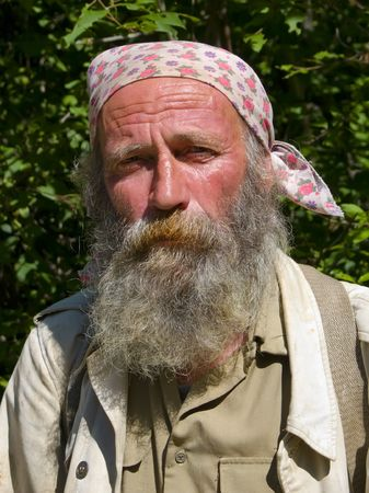 A portrait of the old weather-burned smiling man with big grey beard. Sunny day, summer. Russian Far East, Primorye. Stock Photo - 3217720