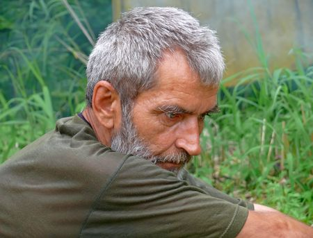 intent: A portrait of the weather-burned man with grey beard and intent look. Profile. Russian Far East, Primorye.