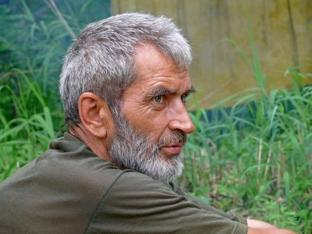 A portrait of the weather-burned man with grey beard and intent look. Profile. Russian Far East, Primorye.