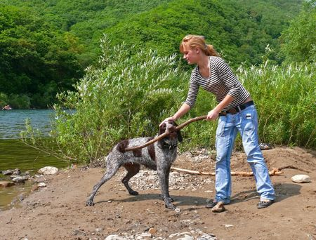 A young girl plays with dog at river. Summer, sunny day. Russian Far East, Primorye.