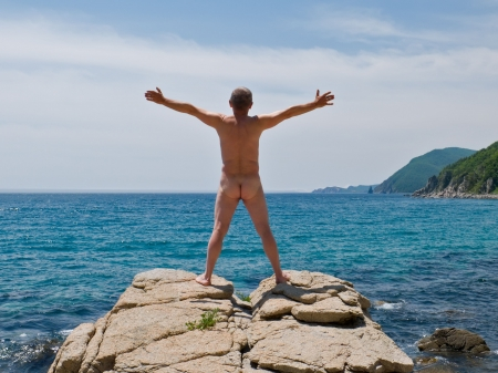 nudist: A  man sunburns on top of rock at seacoast. View from back.  On background is azure seawater and capes. Russian Far East, Primorye, Japanese sea.