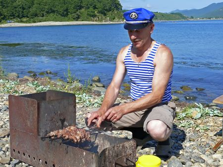 The man in singlet cooks a shashlik at seacoast. Summer, sunny day. Russian Far East, Primorye.