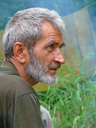 A portrait of the weather-burned man with grey beard and intent look. Profile. Russian Far East, Primorye. Stock Photo - 3374022