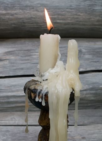A close-up of a burning and melting candle. On background is old wooden wall.