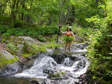 woodsy: A woman stands at very small waterfall on small woodsy river. Russian Far East, Primorye, state nature reserve Lazovsky, Suchoy spring.