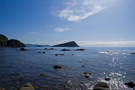 seacoast: A landscape on Japanese sea. On foreground is seawater with stones. On background are small island and blue sky with white clouds. Stock Photo