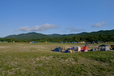 seacoast: A camp of touristes on broad meadow at seacoast. On background are green hills and blue sky with clouds.
