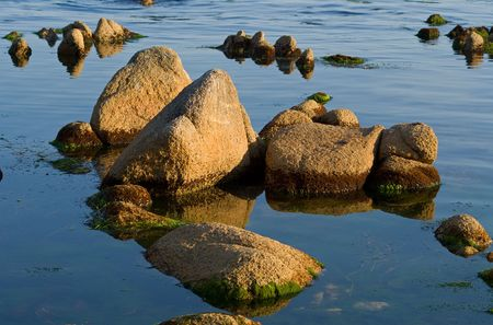 seawater: A close-up of the brown-red stones in seawater. Summer, early evening. Stock Photo