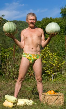 cucurbit: A man stands with two pepos in his hands. At his feet are vegetable marrows and box with tomatos.