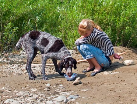 A young girl feeds a dog at river bank. Summer, sunny day. Russian Far East, Primorye. Stock Photo