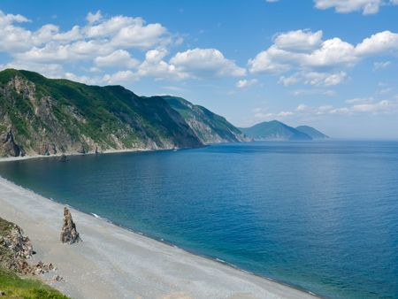 inlet bay: A landscape at sea. Grey beach; green mountains and capes; azure sea; white clouds. Summer. Japanese sea, Russian Far East, Primorye, Tasovaya bay.