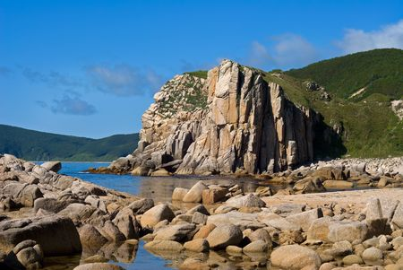 A rocky cliff on Japanese sea. On foreground are seawater with many stones. Summer, sunny day. A name of cliff is