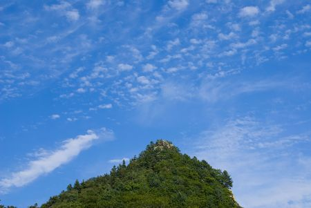 clearness: A cloudy sky above top of green mountain. Seacoast of Japanese sea.