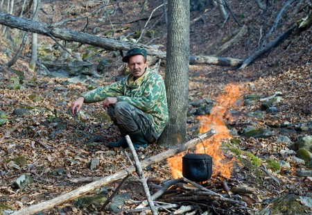 A man is at bonfire in forest. Above fire is pot. Stock Photo - 3942371
