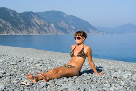 capes: A girl sunburns on seabeach with grey-blue pebbles. On background are seawater and capes. Stock Photo