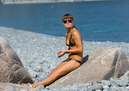 sunburned: A girl sunburns on big stone on seabeach with grey-blue pebbles. On background is seawater. Stock Photo