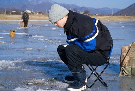 A boy on winter fishing on river. People is fishing the smelt. Stock Photo