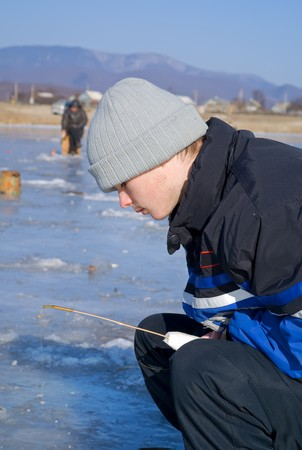 handline fishing: A boy on winter fishing on river. People is fishing the smelt. Stock Photo