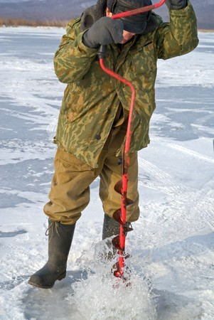 hobbyist: Winter fishing on river. A man drills a hole in ice.