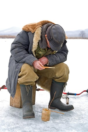 Winter fishing on river. People is fishing the smelt. photo