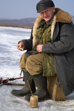 hobbyist: Winter fishing on river. People is fishing the smelt.