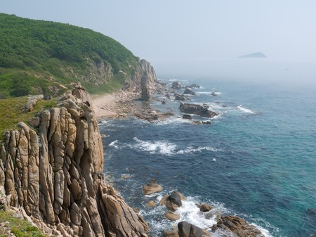 A rocky cliff on Japanese sea. On background are surf and rocks in fog.
