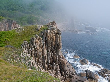 seacoast: A rocky cliff on Japanese sea. On background are surf and rocks in fog.