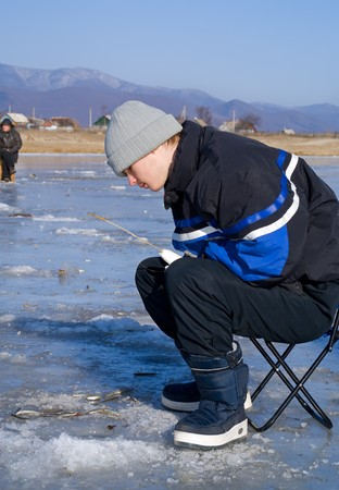 hobbyist: A boy on winter fishing on river. People is fishing the smelt. Stock Photo