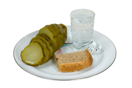 A close-up of the glass of vodka, pickled cucumber and piece of black bread. Stock Photo