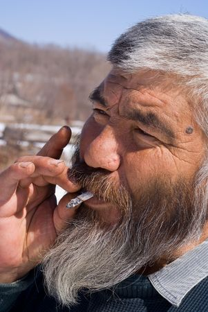 A portrait close-up of the old smoking men with grey beard. Small indigenous people of Russian Far East. photo