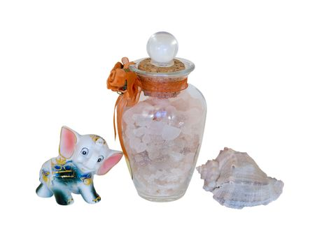 A close-up of the aromatic salt for bath, toy china elephant and marine shell. photo