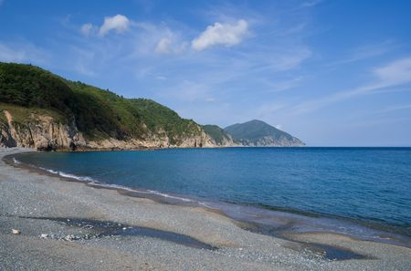 capes: A landscape on Japanese sea. A beach with grey pebbles< green capes and cloudy sky.