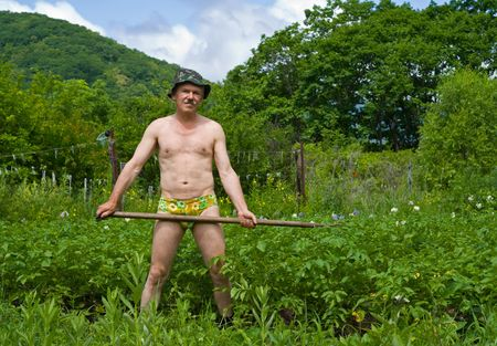 A man weeds garden-bed with hoe.