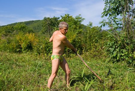 mows: A man mows a grass with a scythe on green meadow. September, sunny day
