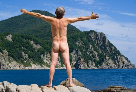 A nude man sunburns on rock on seacoast. View from back. Stock Photo