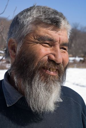 A portrait close-up of the old smiling men with grey beard. Small indigenous people of Russian Far East. Stock Photo - 5564648