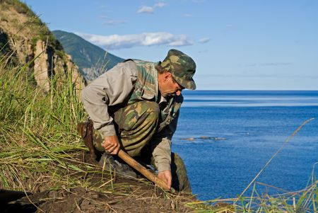 archeologist: The archeologist digs ground at sea. He explores new places for Institute of Archeology and Ethnography (Vladivostok). Stock Photo